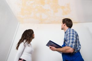 A Plumber and Customer Looking at a Water Stain on the Ceiling.